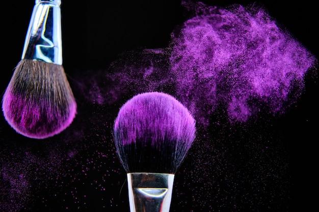 Hermosa foto de pincel de maquillaje aislado sobre fondo negro