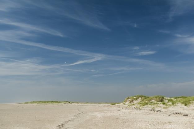 Hermosa foto de una playa de arena bajo un cielo azul claro
