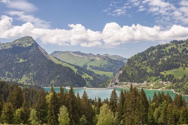 Hermosa foto de la presa de lac de l'hongrin con montañas bajo un cielo despejado
