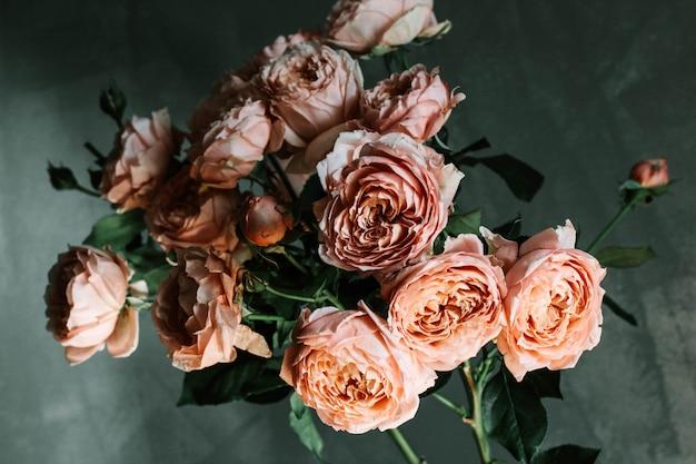 Hermosa foto de primer plano selectivo de rosas de jardín de color rosa en un florero de vidrio