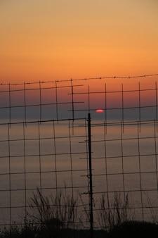 Hermosa foto de la puesta de sol sobre el océano detrás de la valla metálica en creta