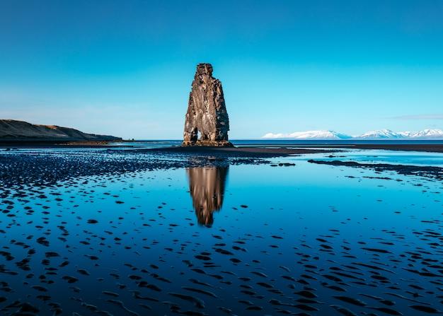 Una hermosa foto de una sola roca en medio de un lago