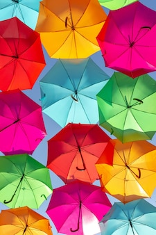 Hermosa foto de sombrillas flotantes multicolores contra el cielo azul