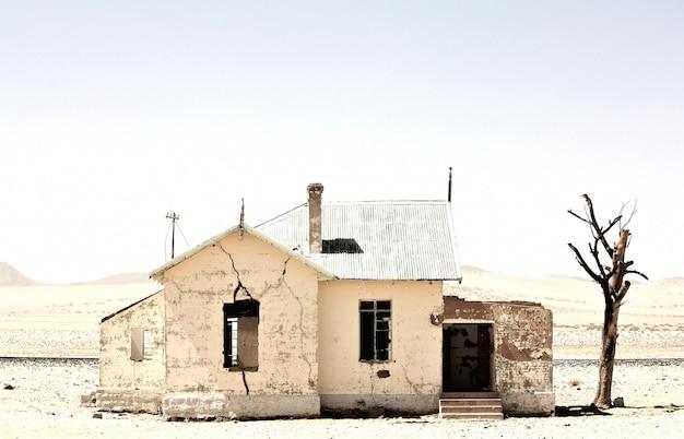 Hermosa foto de una vieja casa abandonada en medio de un desierto cerca de un árbol sin hojas