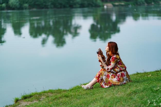 Hermosa fotógrafa pelirroja toma fotos con una vieja cámara