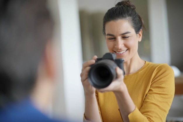 Hermosa fotógrafa profesional tomando fotos de una modelo.