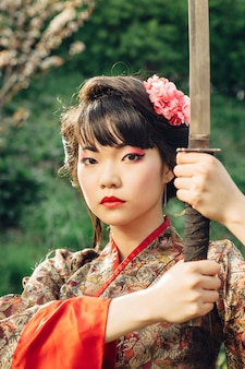 Hermosa geisha en kimono con espada samurai