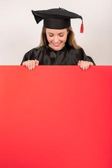 Hermosa graduada sosteniendo cartel rojo maqueta