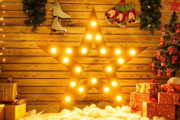 Hermosa gran estrella se levanta contra la pared y brilla, brillando en la decoración navideña.