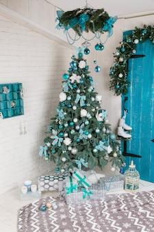Hermosa habitación decorada con árboles de navidad y regalos debajo