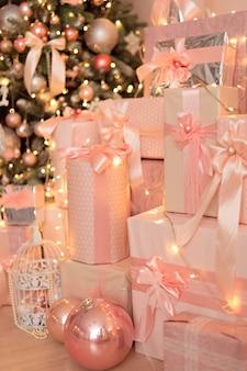 Hermosa habitación decorada festivamente de color rosa con un árbol de navidad, regalos. año nuevo.