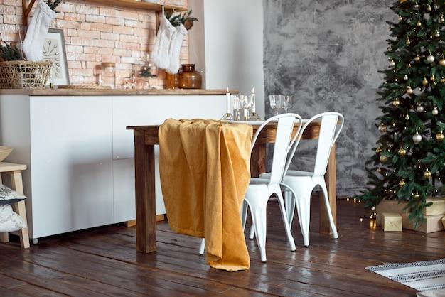 Hermosa habitación decorada festivamente de estilo escandinavo, una mesa festiva con una mesa y un árbol de navidad con regalos debajo.