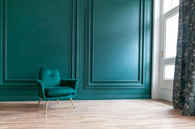 Hermosa habitación interior limpia de lujo clásico azul verde en estilo clásico con sillón verde suave. silla antigua vintage azul-verde de pie junto a la pared esmeralda. diseño de hogar minimalista.