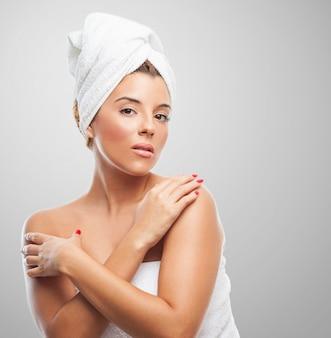 Hermosa hembra con la cabeza torcida en una toalla.