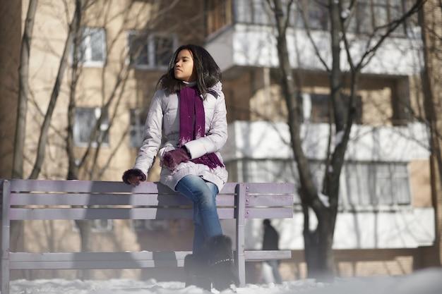 Hermosa hembra negra americana en la calle invierno sentado en un banco