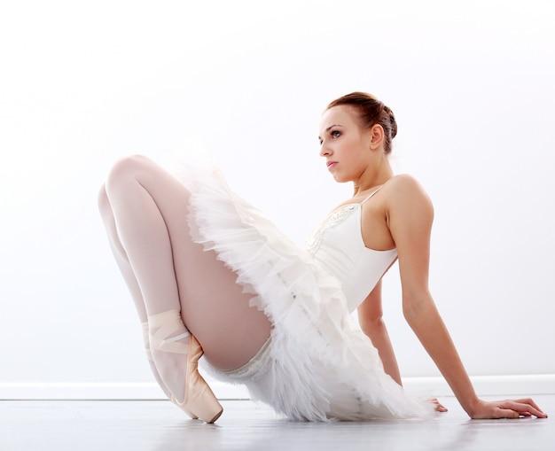 Hermosa y hermosa bailarina sentada en el piso