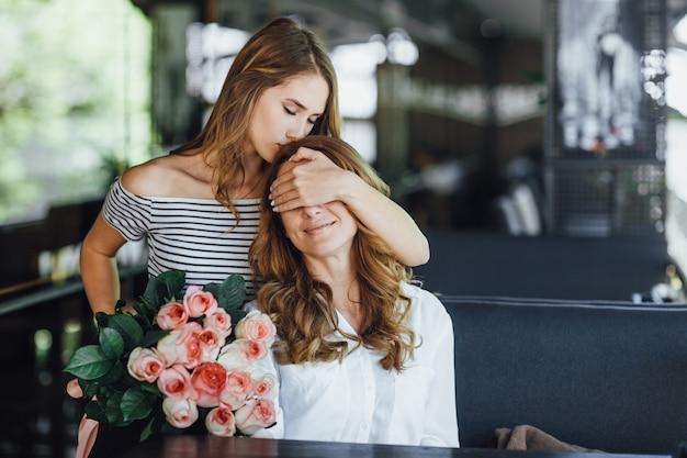 Hermosa hija adolescente cierra los ojos de su madre y le da un ramo de rosas