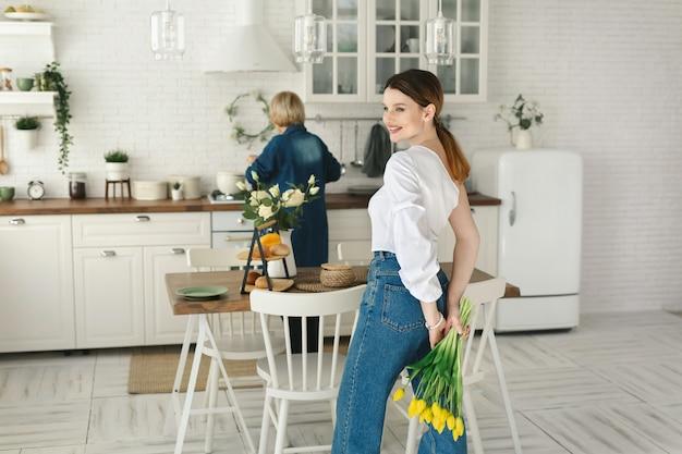 Hermosa hija adulta esconde flores a sus espaldas para su madre adulta. día de la madre, fiesta de mujeres.