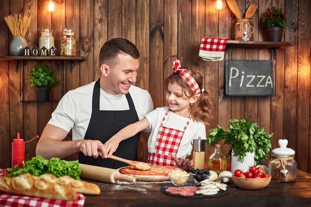 Hermosa hija ayudando a papá a untar salsa mientras cocina pizza