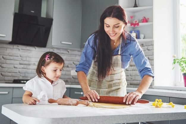 Una hermosa hija con su madre cocinando en la cocina