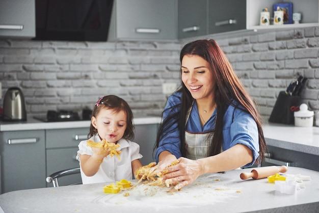 Una hermosa hija con su madre hornea.