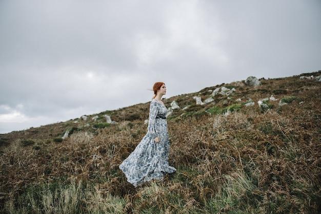 Hermosa imagen de una mujer pelirroja con una piel blanca pura en un atractivo vestido azul claro