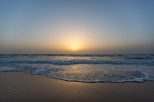 Hermosa imagen de una puesta de sol desde una playa bajo un cielo azul en senegal