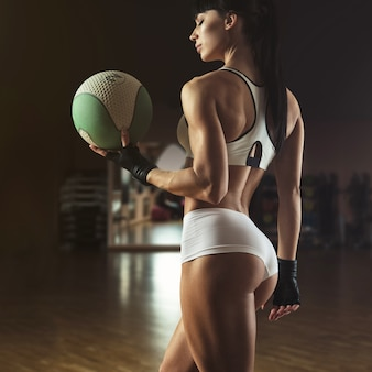 Hermosa instructora de pilates sosteniendo una pelota de fitness
