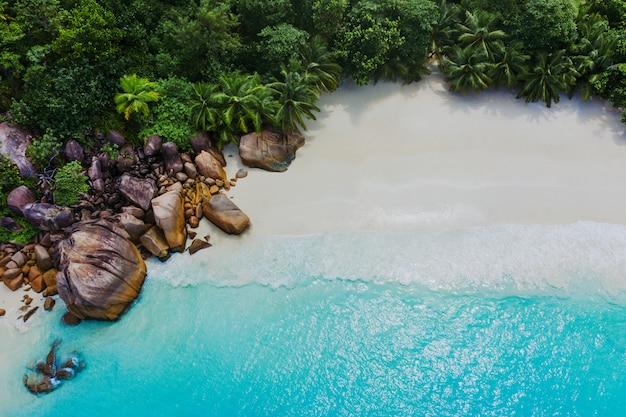 Hermosa isla en las seychelles. la digue, playa de anse d'argent. el agua fluye y las olas hacen espuma en un paisaje tropical