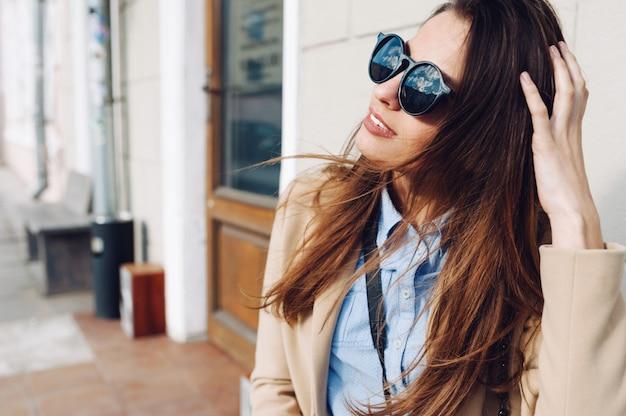 Hermosa y joven con un abrigo y bufanda y gafas de sol sentado en el banco