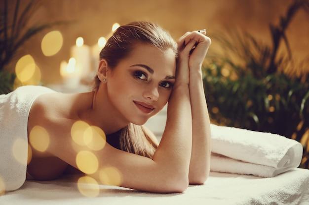 Hermosa joven acostada y esperando su masaje. concepto de spa