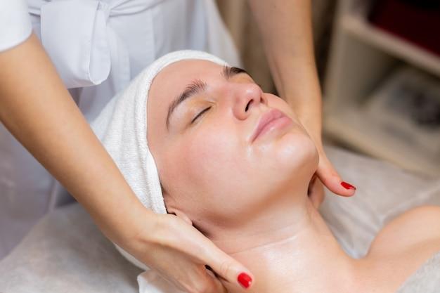 Una hermosa joven se acuesta en la mesa de la esteticista y recibe procedimientos, un ligero masaje facial con aceite.