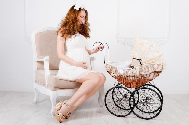 Hermosa joven adolescente embarazada en vestido blanco con carro de bebé está sentado en una silla clásica suave