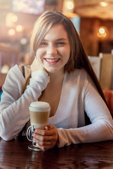 Hermosa joven adolescente sonriente sentada en la cafetería o bar y beber latte macchiato.