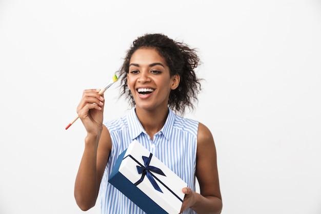 Hermosa joven africana de pie sobre blanco, sosteniendo la caja de regalo, mostrando el pincel