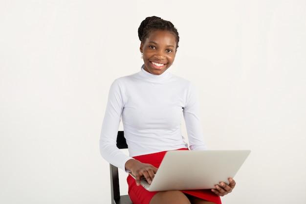 Hermosa joven africana con un portátil