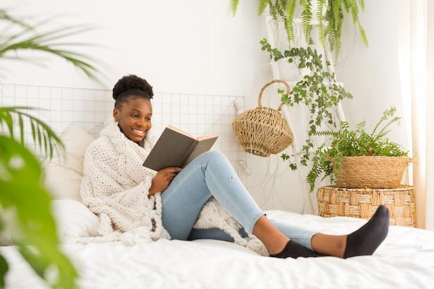 Hermosa joven africana sentada en la cama con un libro