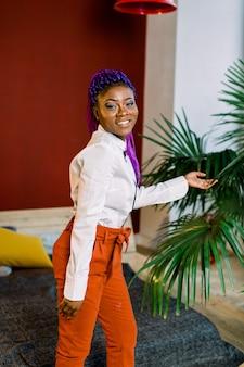 Hermosa joven afroamericana, posando en el interior, con el pelo azul. vestido con blusa blanca y pantalón naranja.