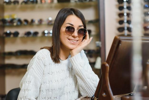 Hermosa joven ajustando sus nuevas gafas de sol de pie en la tienda óptica