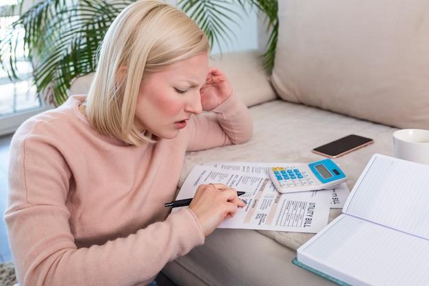 Hermosa joven albino mujer sentada con calculadora y facturas, haciendo papeleo.