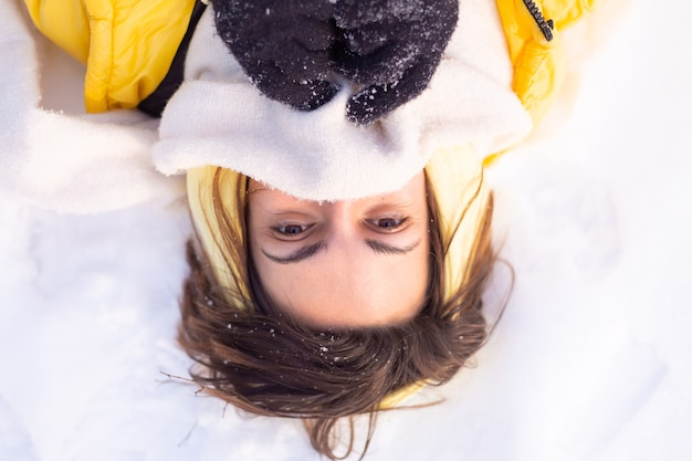 Hermosa joven alegre en un bosque de invierno paisaje nevado divirtiéndose se regocija en invierno y nieve en ropa de abrigo, bufanda