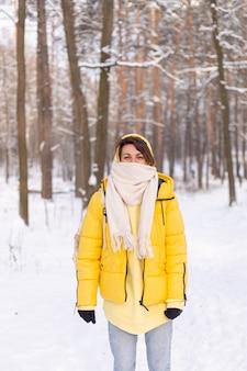 Hermosa joven alegre en un bosque de invierno paisaje nevado divirtiéndose se regocija en invierno y nieve en ropa de abrigo