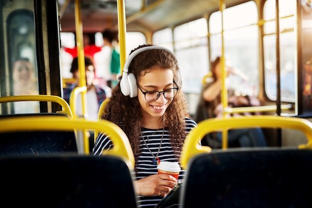 Una hermosa joven alegre con cabello rizado está sentada en el asiento del autobús escuchando música tomando café y usando una tableta.