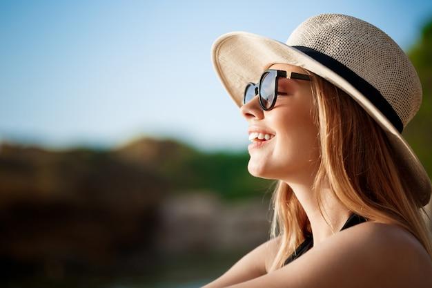 Hermosa joven alegre con gafas y sombrero descansa en la playa de la mañana