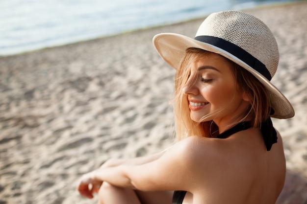 Hermosa joven alegre con sombrero descansa en la playa de la mañana
