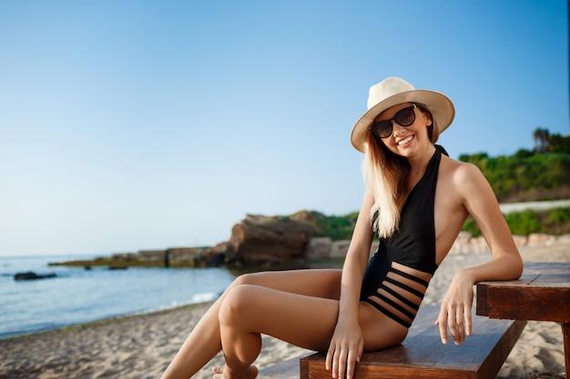 Hermosa joven alegre en sombrero y gafas de sol descansa en la playa de la mañana