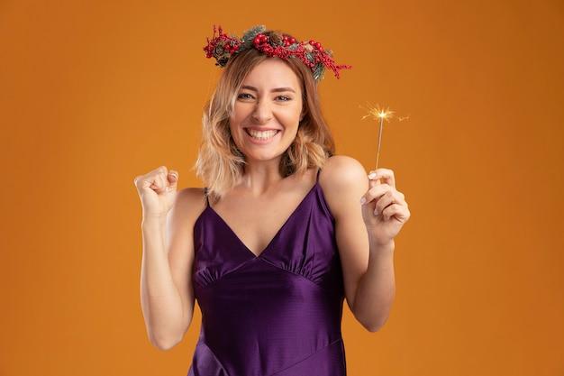 Hermosa joven alegre con vestido púrpura con corona sosteniendo luces de bengala mostrando sí gesto aislado sobre fondo marrón