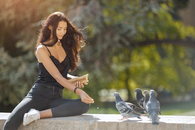 Hermosa joven alimentando palomas