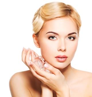 Hermosa joven aplica el hielo a la cara. concepto de cuidado de la piel. aislado en blanco.