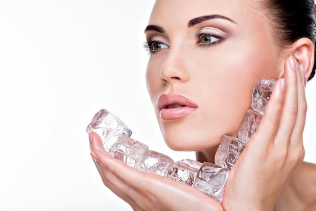 Hermosa joven aplica el hielo a la cara. concepto de cuidado de la piel.